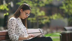Beautiful student in glasses with a digital tablet sitting outdoor. Elegant young girl using the tablet. Beautiful student in glasses with a digital tablet stock footage