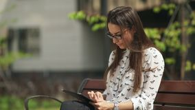 Beautiful student in glasses with a digital tablet sitting outdoor. Elegant young girl using the tablet. Beautiful student in glasses with a digital tablet stock video
