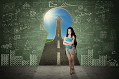 Beautiful student and a keyhole Royalty Free Stock Image