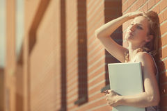 Beautiful student with laptop relaxing outside library Royalty Free Stock Photo