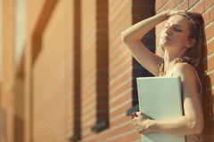 Beautiful student with laptop relaxing outside library Stock Photo
