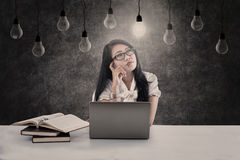 Beautiful student looking at lit bulb Stock Photo