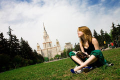 Beautiful student reading book. In front of Moscow State University Stock Photo