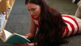 Beautiful student reading a book lying on the floor. In the library stock video