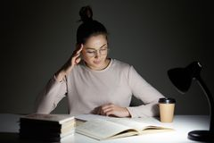 Beautiful student sits at white desk against dark background, tries to concentrate under light of lamp, wears casual jamper and