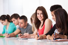 Beautiful student sitting with classmates writing at desk Stock Photo