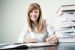 Beautiful student smiling. Beautiful student siiting at table smiling. With books on desk Stock Photo