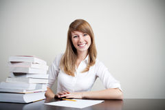 Beautiful student smiling. Successful student sitting at desk smiling with books on table Stock Photos