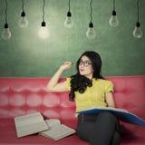 Beautiful student studying under light bulb Royalty Free Stock Photos