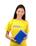 Beautiful student with Sweden flag on the yellow blouse holding books Stock Image