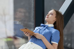 Beautiful student. With tablet looking at the window Royalty Free Stock Image