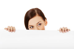 Beautiful student woman hiding her face behind blank banner.  Stock Photography
