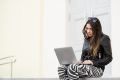 Beautiful student woman is smiling using a laptop and sitting on old wall in the university campus. Gorgeous girl stock photos