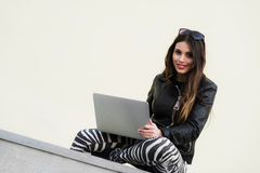 Beautiful student woman is smiling using a laptop and sitting on old wall in the university campus. Gorgeous girl stock image