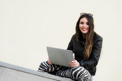 Beautiful student woman is smiling using a laptop and sitting on old wall in the university campus. Gorgeous girl royalty free stock images