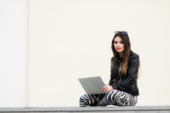 Beautiful student woman is smiling using a laptop and sitting on old wall in the university campus. Gorgeous girl royalty free stock photography