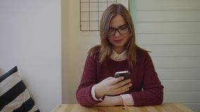 Beautiful student woman using smartphone in cafe. 4K stock video