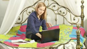 Beautiful student working on her laptop. on-line education in home.  stock video footage