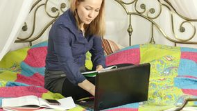 Beautiful student working on her laptop. on-line education in home.  stock video
