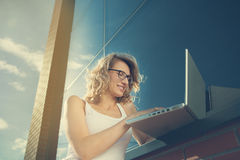 Beautiful student working with laptop next to the brick-wall. Royalty Free Stock Image