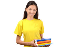 Beautiful student in yellow blouse holding books. Royalty Free Stock Images
