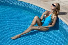 Beautiful stunning elegant sexy blonde model woman with perfect face wearing a sunglasses in a pool with elegant bikini. On amazing view  in Cannes, France Royalty Free Stock Photos