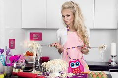 Beautiful stunning funny blonde woman dressed in costume cook cooks in the kitchen. Noodles pasta Royalty Free Stock Photos