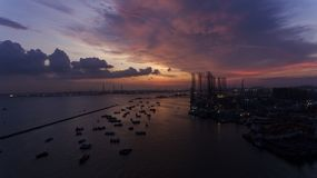 Beautiful, stunning sunset over the water, over boats in an industrial looking dock or port. royalty free stock photos