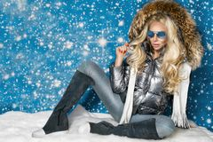 Beautiful stunning woman with long blond hair and perfect face dressed in winter clothing, silver warm jacket , sunglasses and cap royalty free stock images