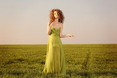 Beautiful styled woman with a long green dress on fields Royalty Free Stock Images