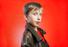 Beautiful stylish blond boy wearing leather coat posing Royalty Free Stock Image