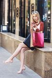 Beautiful stylish blonde woman holding paper bag and using smartphone while sitting. On street stock photo