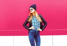 Beautiful stylish blonde woman in rock black style jacket, hat posing on city street over colorful pink wall royalty free stock photos