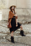 Beautiful stylish boho woman with hat, leather bag, fringe poncho and boots. girl in gypsy hippie look young traveler posing near. River rocks in mountains stock photo