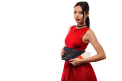 Beautiful stylish brunette girl in red dress holds a clutch in hands Royalty Free Stock Images