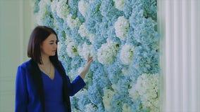 Brunette girl in blue walking next to flower wall slow motion