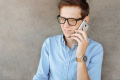 Beautiful stylish business guy with glasses, posing on the beach, hipster talking on the phone, work on vacation, for advertising, royalty free stock image