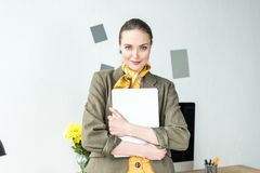 beautiful stylish businesswoman holding laptop and smiling at camera stock photos