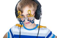 Beautiful stylish child wearing big headphones and. Portrait of a beautiful stylish preschool child wearing big headphones and funny glasses posing  (music Royalty Free Stock Photography