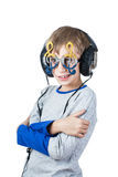 Beautiful stylish child wearing big professional headphones and funny glasses listens to music Royalty Free Stock Photography