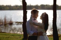 Beautiful, stylish couple hugging near the river at sunset, the bride and groom admire each other, look into the eyes.  royalty free stock photography