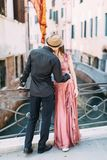 Beautiful stylish couple walking on the bridge of venetian canal in Venice, Italy royalty free stock photo