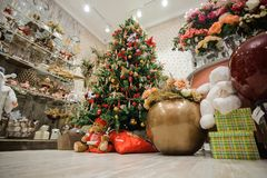 Beautiful decorated Christmas tree in a shop. Beautiful and stylish decorated Christmas tree in a flower shop with bouquets and cute souvenirs Royalty Free Stock Image
