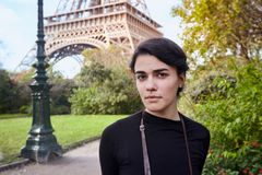 Beautiful dreamy girl posing on the background of the Eiffel Tower. Paris, Champ de Mars. Beautiful stylish, dreamy girl in black dress with backpack posing on stock photography