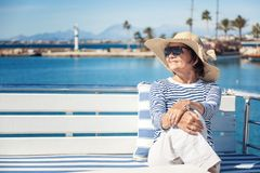 Beautiful stylish elderly woman travels on a yacht, on a backgro. Und of a resort and the sea. Active pensioners, vacations, travel Royalty Free Stock Images