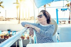 Beautiful stylish elderly woman travels on a yacht, on a backgro. Und of a resort and the sea. Active pensioners, vacations, travel Royalty Free Stock Photos