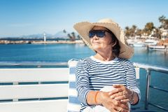 Beautiful stylish elderly woman travels on a yacht, on a backgro. Und of a resort and the sea. Active pensioners, vacations, travel Stock Images