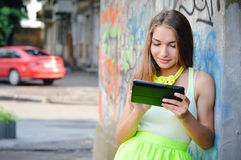 Beautiful stylish fashion blond woman on tablet pc. Beautiful blonde stylish fashion woman reading message on tablet pc at graffiti wall Stock Images
