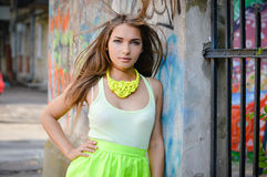 Beautiful stylish fashion woman at graffiti wall in city with flying hair Stock Photo