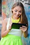 Beautiful stylish fashion woman reading message on tablet pc at graffiti wall Royalty Free Stock Photo